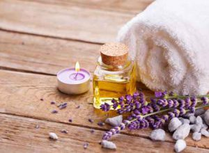 Spa still life with lavender oil, white towel and perfumed candl